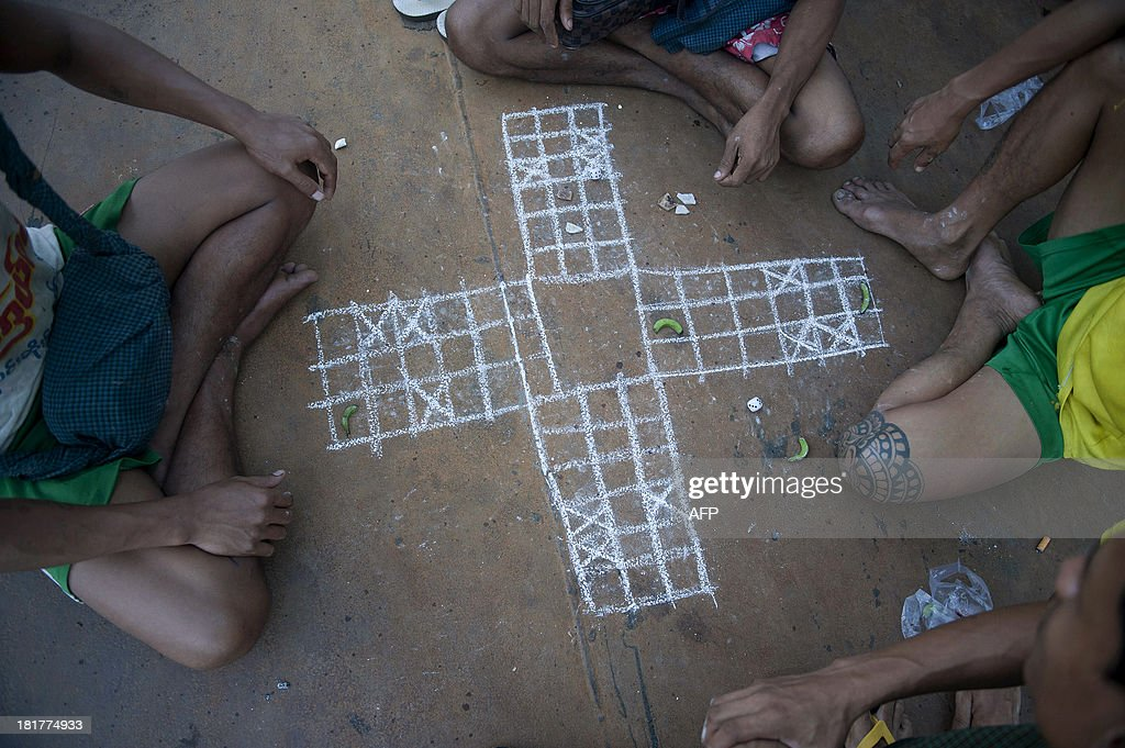 This picture taken on September 24, 2013 shows labourers playing a game with banana-shaped pawns at a jetty in Yangon. Myanmar has the potential to quadruple the value of its economy to 200 billion USD by 2030 if it presses on with reforms, embraces technology and shifts away from agriculture, a study said recently. AFP PHOTO/Ye Aung THU