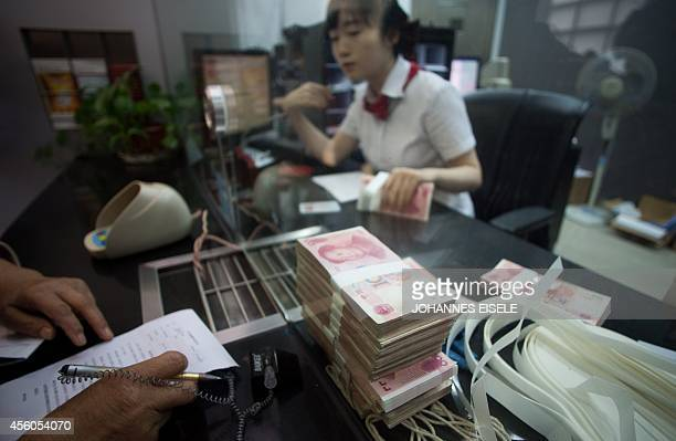 This picture taken on September 24 2014 shows a worker of an Industrial and Commercial Bank of China Ltd branch counts money as she serves a customer...