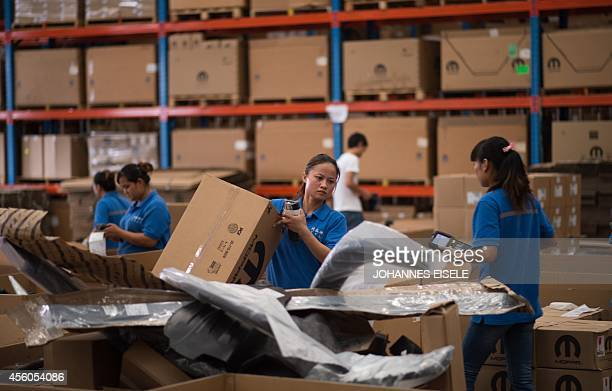 This picture taken on September 24 2014 shows workers packing goods at a warehouse of TSLP at the China Pilot Free Trade zone during a media trip...
