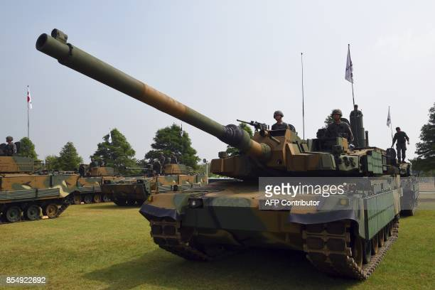 This picture taken on September 25 2017 shows South Korean soldiers sitting on a K2 tank during a media day presentation of a commemoration event...