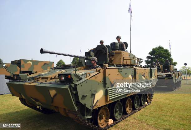 This picture taken on September 25 2017 shows South Korean soldiers sitting on a K21 Infantry fighting vehicle during a media day presentation of a...