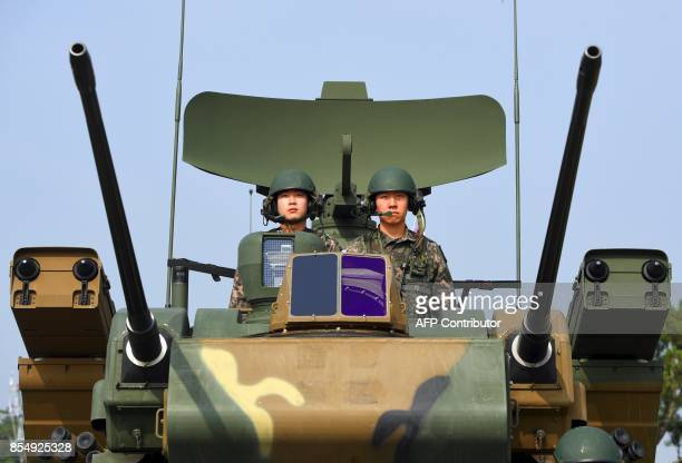 This picture taken on September 25 2017 shows South Korean soldiers sitting on a K30 Biho twin 30 mm selfpropelled antiaircraft weapon during a media...