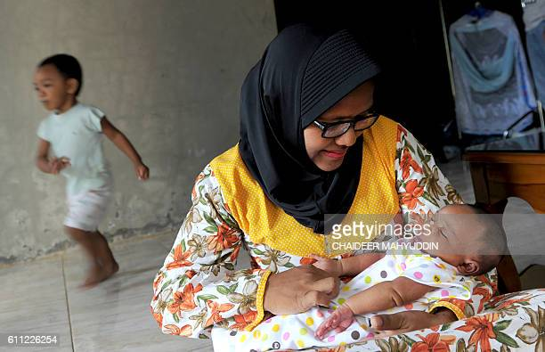 This picture taken on September 28 2016 shows Yenni Linda Yanti a nurse at a government hospital in Aceh with her newborn baby being the first mother...