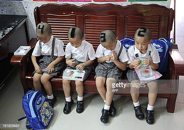 This picture taken on September 3 shows sixyearold quadruplets from Shenzhen south China's Guangdong Province with their hair shaved into various...