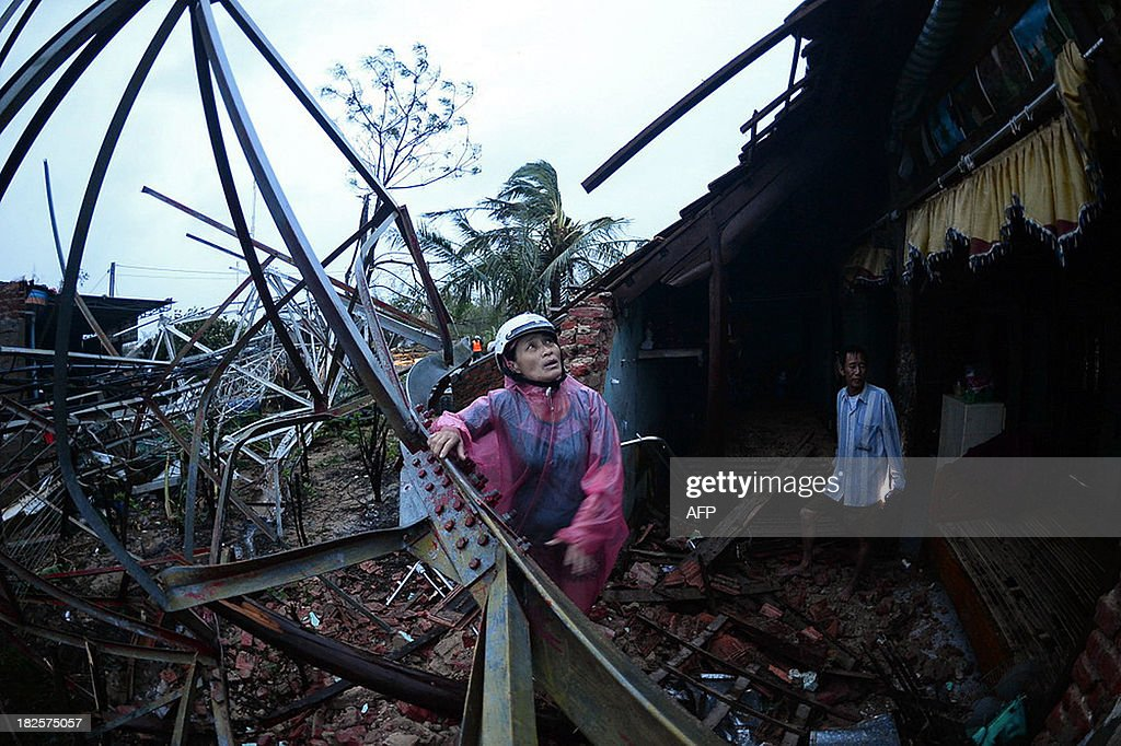 This picture taken on September 30, 2013 shows a woman inspecting the damage triggered by the collapse of a telecommunications antenna on the house where she was hiding from Typhoon Wutip with her three children in the Quang Ninh district of Vietnam's central Quang Binh province. At least three people were killed and 26 others injured as Typhoon Wutip slammed into central Vietnam, leaving more than 70 fishermen missing and a trail of devastation in its wake, reports said on October 1, 2013. AFP PHOTO / TUOI TRE NEWSPAPER