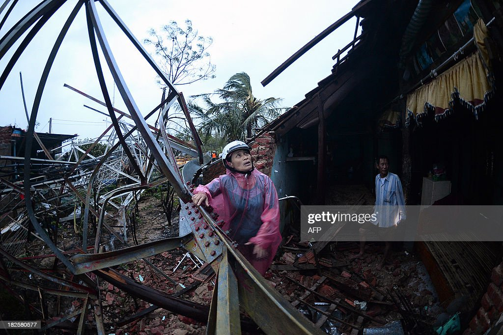 This picture taken on September 30, 2013 shows a woman inspecting the damage triggered by the collapse of a telecommunications antenna on the house where she was hiding from Typhoon Wutip with her three children in the Quang Ninh district of Vietnam's central Quang Binh province. At least three people were killed and 26 others injured as Typhoon Wutip slammed into central Vietnam, leaving more than 70 fishermen missing and a trail of devastation in its wake, reports said on October 1, 2013.