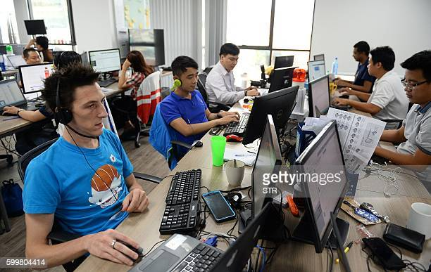 This picture taken on September 5 2016 shows French and Vietnamese employees working inside the French IT company Linkbynet in Ho Chi Minh City A...