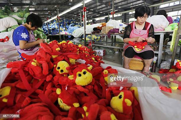 This picture taken on September 6 2015 shows Chinese workers putting the finishing touches on soft toys at a factory before packing them for export...