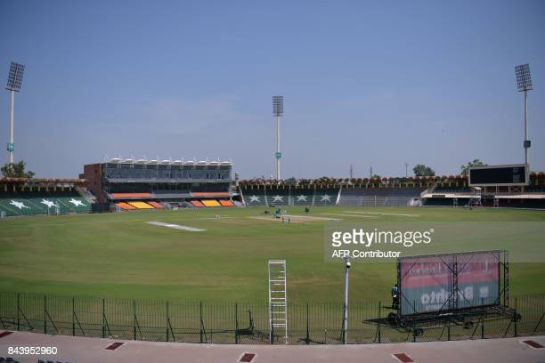 This picture taken on September 7 2017 shows ground staff preparing the cricket pitch of the Gaddafi Stadium in Lahore Groundsmen are rolling down...