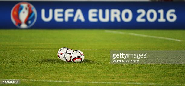 This picture taken on September 8 2014 shows three balls on the pitch in front of a UEFA logo prior to the UEFA Euro 2016 Group E qualifying football...