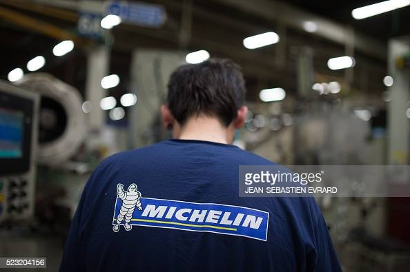 This picture taken on shows an employee of French tyre maker 'Michelin' wearing a sweater with the brand's logo on April 22 2016 at the Michelin...