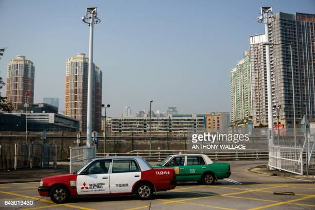 This picture taken outside the Lok Ma Chau MTR station in Hong Kong on February 13 2017 shows taxis driving past a border fence that separates Hong...