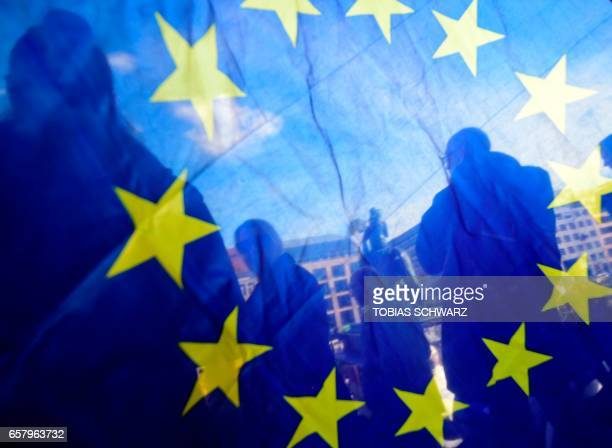 TOPSHOT This picture taken through an EU flag shows people attending a proEurope demonstration in Berlin on March 26 2017 / AFP PHOTO / Tobias SCHWARZ