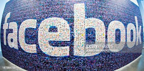 This picture taken with a fisheye lens shows a man walks past a big logo created from pictures of Facebook users worldwide in the company's Data...
