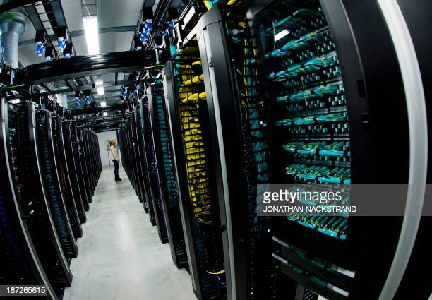 This picture taken with a fisheye lens shows a woman stands next to servers in one of the server rooms of the new Facebook Data Center its first...
