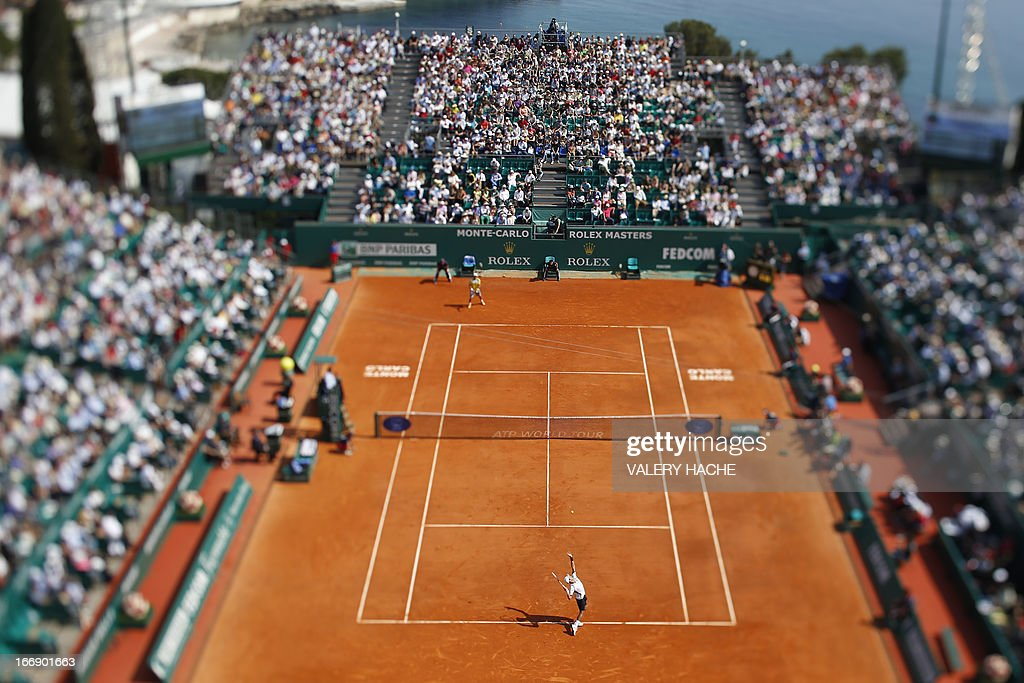 This picture taken with a tilt and shift lens shows Serbia's Novak Djokovic (C) serving to Argentina's Juan Monaco during their Monte-Carlo ATP Masters Series Tournament tennis match on April 18, 2013 in Monaco. Djokovic won 4-6, 6-2, 6-2 and is qualified for the quarter-finals.