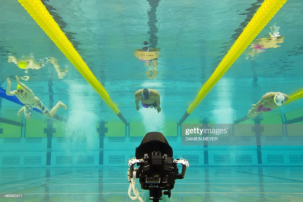 This picture taken with an underwater camera shows swimmers competing in the 100m breaststroke men's race on April 8, 2014 during the French swimming championships in Chartres. AFP PHOTO / DAMIEN MEYER