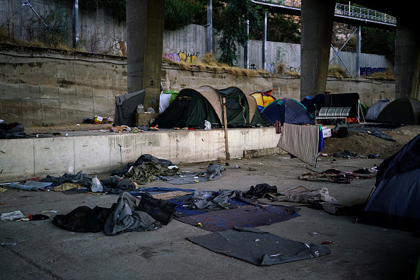 This picture tkaen on July 17, 2016 shows tents and blankets on the ground in the port of Piraeus, where nearly 1,500 refugees and migrants live in a make-shift camp in Athens on July 17, 2016. In ...