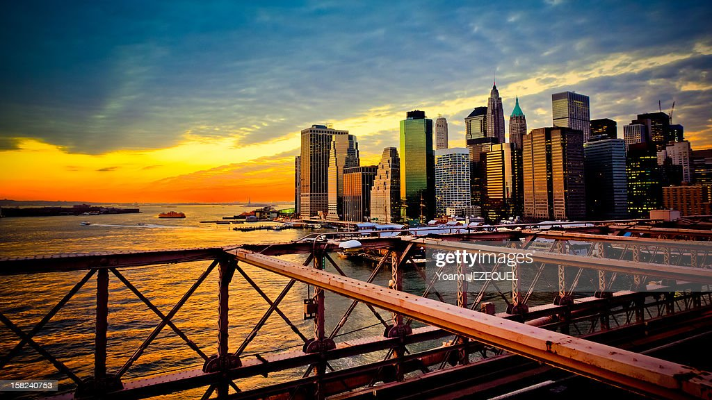 This picture was taken from the Brooklyn Bridge at the sunset during the winter. The view of Manhattan (New York City) was stunning! The sunset light reflected on the buildings and skyscrapers of New York City. This picture is a symbol of New York City. This cliche of the big apple was taken during an holidays week in USA. The monuments of New York City are wonderful and you can discover many tourist places! You can see the Statue of Liberty far far away on the background of the image. She seems tiny compared to the buildings!! About the Brooklyn Bridge, it is the oldest suspension bridges in the United States. Completed in 1883, it connects the borough of Manhattan and Brooklyn by spanning the East River. Cette photographie a été réalisée du Pont de Brooklyn pendant un coucher de soleil sur New York. La lumière se reflétait sur les immeubles et gratte-ciels de Manhattan. Pour information, le Pont de Brooklyn est le plus ancien pont suspendu des Etats-Unis. Il relie les quartiers de Manhattan et de Broolkyn en enjambant l East River.