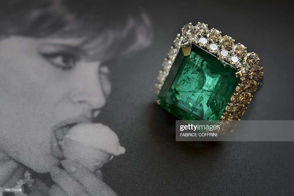 This piucture taken on May 7, 2013 shows an emerald and diamond ring by Bulgari 1964 (estimate CHF 115'000-170'000, USD 120'000-180'000) next to a picture of Italian actress Gina Lollobrigida during a press preview of auction house Sotheby's in Geneva. Lollobrigida is to sell some of her jewellery in Geneva on May 14, 2013 with part of the proceeds going to help stem cell research, auction house Sotheby's said. Designed by Italian creator Bulgari in the 1950s and 1960s, the items include pearl and diamond earrings and a 19.3-carat diamond ring. Both pieces are valued at between $600,000 and one million dollars (465,000 - 775,000 euros). The 85-year-old star of 'The World's Most Beautiful Woman' and 'Come September,' one of Italy's best-known actresses, says she wants to devote herself to sculpture and 'a sculptor doesn't need jewellery', the Sotheby's statement said.