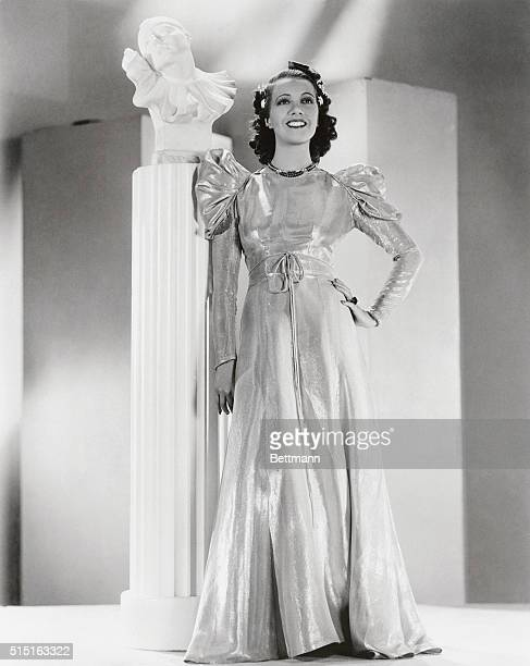 This regal empire gown of gold and orange lame worn by Lily Pons opera and film star was designed by Edward Stevenson to enhance the dusky charms of...