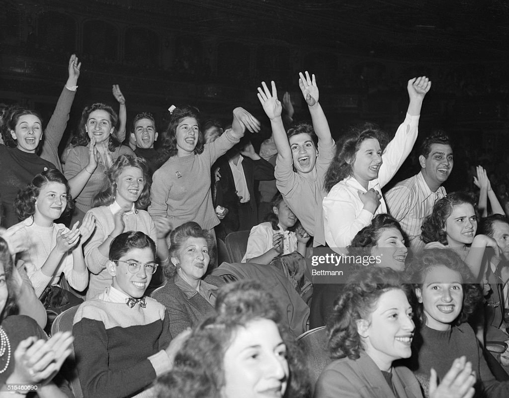 This scene was repeated over and over again as Frnk Sinatra made his first appearance on the stage of the Paramount Theatre this morning. Boys and girls of the 'Bobbysock Brigade' came out en masses to hear their 'Frankie' do his stuff. Girl at right in background closes her eyes, cheers loudly and waves her arms frantically.
