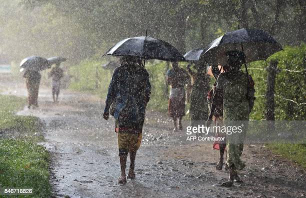 This September 13 2017 photo shows an Indian tea worker returning home through heavy rainfall after work at a tea plantation in Udalguri district of...