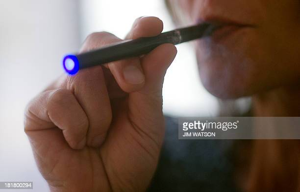 This September 25 2013 photo illustration taken in Washington DC shows a woman smoking an 'Blu' ecigarette The National Association of Attorneys...