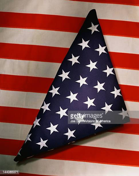 This shows a triangularly folded American flag sitting on top of another American flag which only shows its red and white stripes going in a...