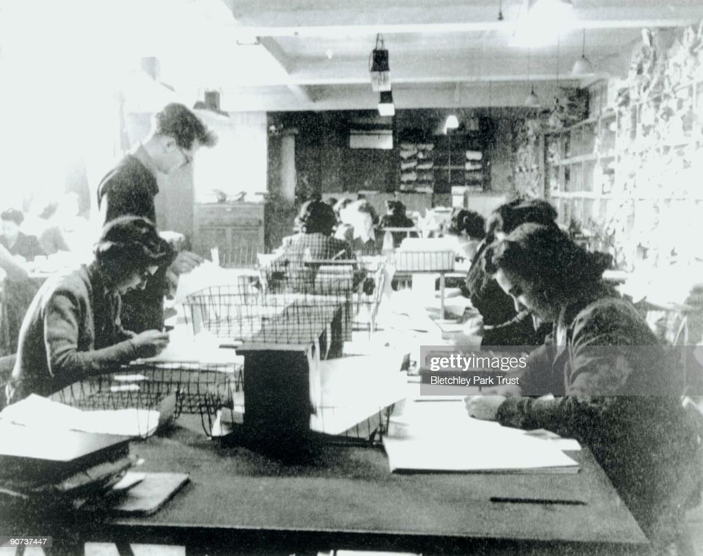 This shows one of the Hut 3 priority teams at Bletchley Park, Buckinghamshire, in which civilian and service personnel worked together at code-breaking. Bletchley Park was the British forces' intelligence centre during WWII, where cryptographers deciphered top-secret military communiques between Hitler and his armed forces. These communiques were encrypted in the 'enigma' code which the Germans considered unbreakable, but the codebreakers at Bletchley cracked the code with the help of 'Bombe' machines.