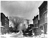 This southerly view of Main Street shows a horse and sleigh parked in the snow in front of a Groton New York storefront | Location Groton New York USA