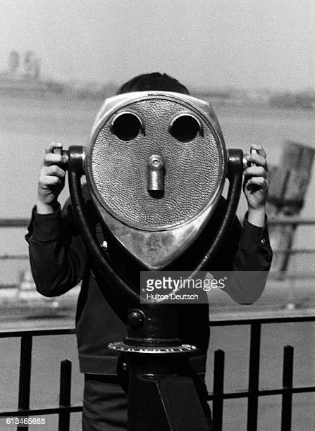 This strange creature is a boy looking through a doublelens telescope located near the Statue of Liberty in New York