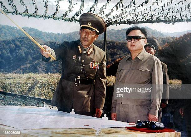 This undated handout files photo acquired in Pyongyang 13 February 2003 shows North Korean leader Kim JongIl being briefed by a field commanders...