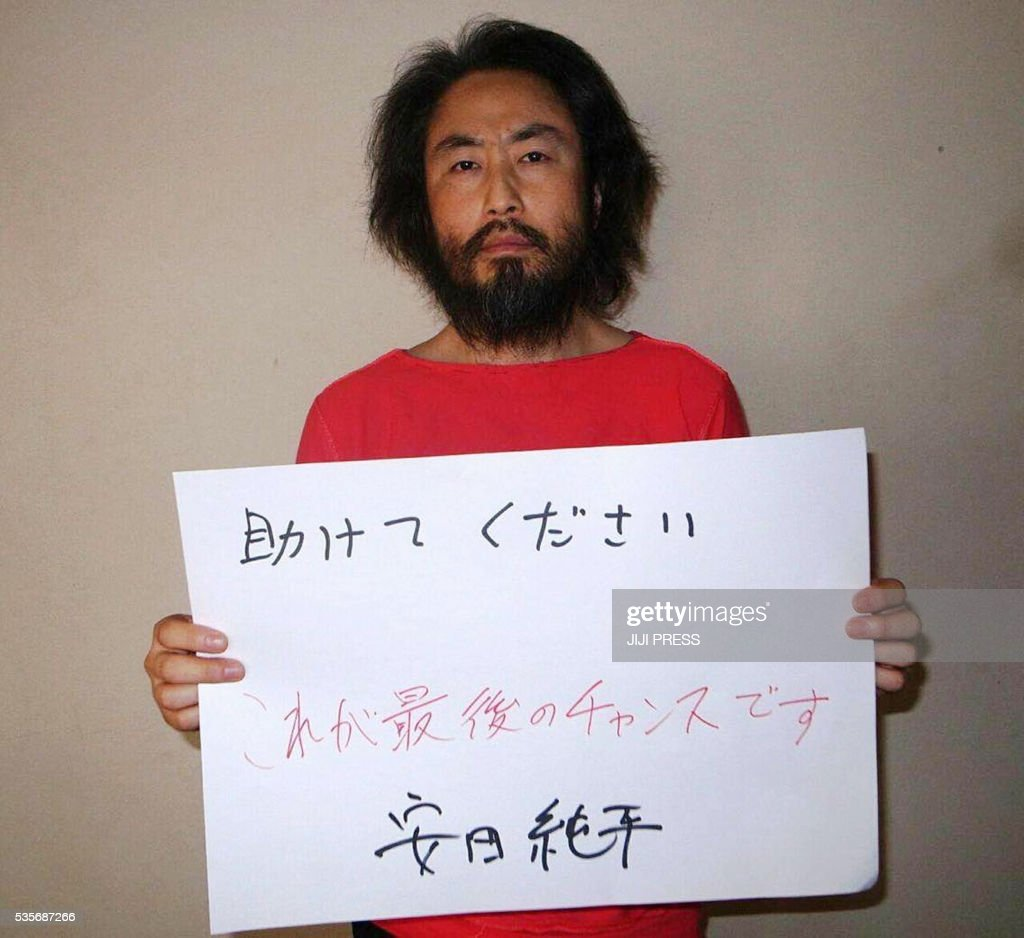 This undated picture released by Japan's Jiji Press news agency, taken at an undisclosed location, on May 30, 2016 shows Japanese freelance journalist Junpei Yasuda holding a piece of paper with a handwritten message in Japanese that says: 'Please help. This is the last chance. Jumpei Yasuda.' The fresh photo, which received widespread coverage in Japanese media on May 30, 2016, shows Yasuda, who has been missing for almost a year, wearing an orange shirt, his hair and beard grown long. / AFP / JIJI PRESS / JIJI PRESS / Japan OUT