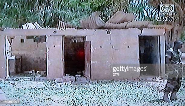 This video grab taken from Niger's TV public channel Tele Sahel on May 23 2013 shows a soldier standing in front of a damaged building at the Agadez...