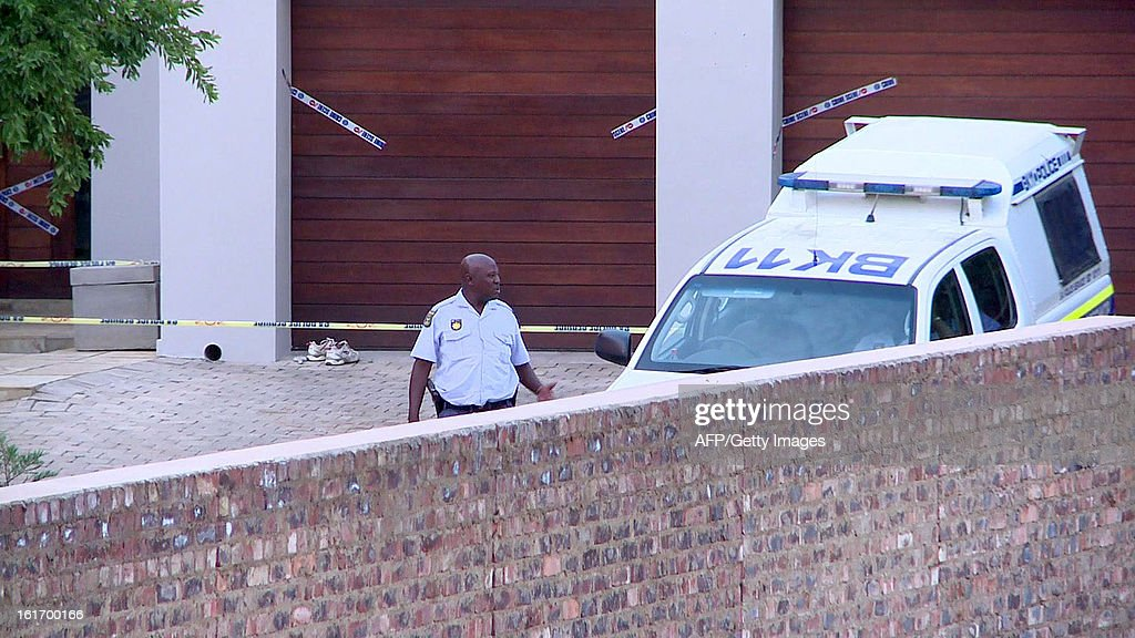 This video image grab taken by AFP TV on February 14, 2013 shows a South African policeman and vehicle stationed outside the house of Olympic amputee sprint star Oscar Pistorius in Pretoria after charging him with the Valentine's Day murder of his model girlfriend, who was shot four times with a gun registered in his name. Police were called to Pistorius's upscale Pretoria home at around 4:00 am by neighbours who heard gunshots inside the gated community.