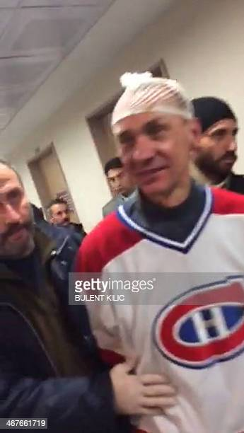 This videograb taken on February 7 2014 shows a man who attempted to hijack an airliner from Ukraine escorted by policemen after the plane was forced...
