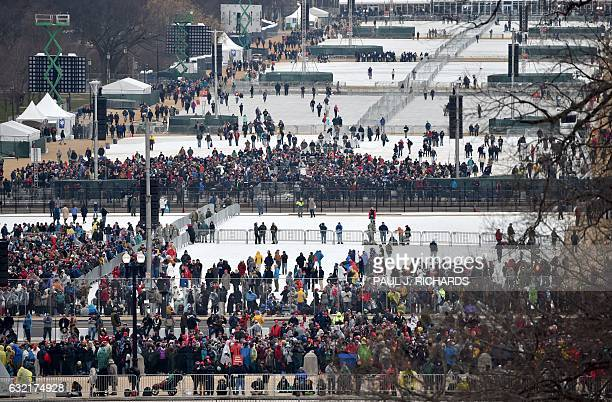 TOPSHOT This view taken January 20 2017 shows people gathering on the mall to witness Presidentelect Donald Trump take the oath of office as the 45th...