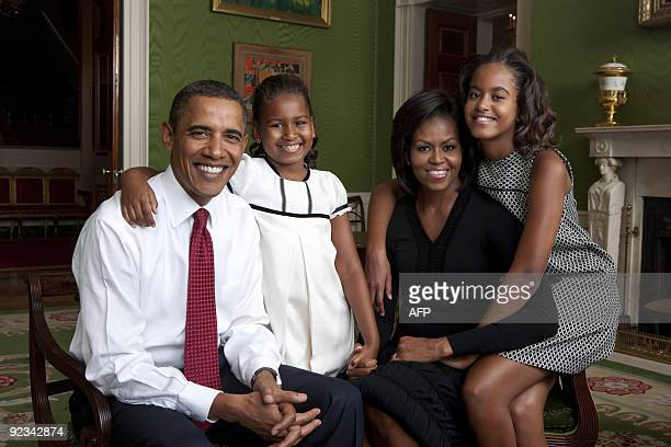 This White House handout photo shows US President Barack Obama First Lady Michelle Obama and their daughters Malia and Sasha as they sit for a family...