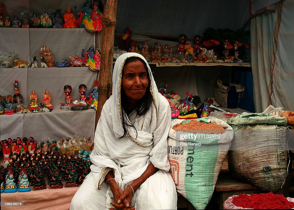 This woman sells hand-made and hand-painted toys at the market. Her white sari indicates she is a widow, since widows are not allowed to wear color in India. Women were also not allowed to use the potter's wheel, so this is unusual to see. Widows were also supposed to shave their heads, and her long hair colored black is another form of resistance.