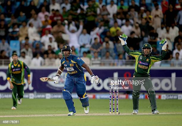 Thisara Perera of Sri Lanka bats as Umar Akmal of Pakistan looks on during the second OneDay International match between Sri Lanka and Pakistan at...