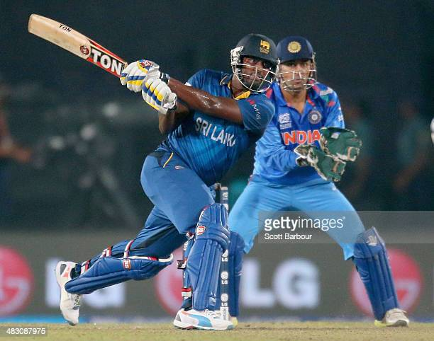 Thisara Perera of Sri Lanka hits the winning runs as MS Dhoni of India looks on during the Final of the ICC World Twenty20 Bangladesh 2014 between...