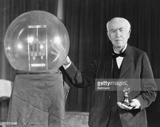 Thomas A Edison exhibits a replica of his first successful incandescent lamp which gave 16 candlepower of illumination in contrast to the ultimate in...