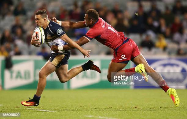 Thomas Banks of the Brumbies is tackled by Chris Kuridrani of the Reds during the round seven Super Rugby match between the Brumbies and the Reds at...