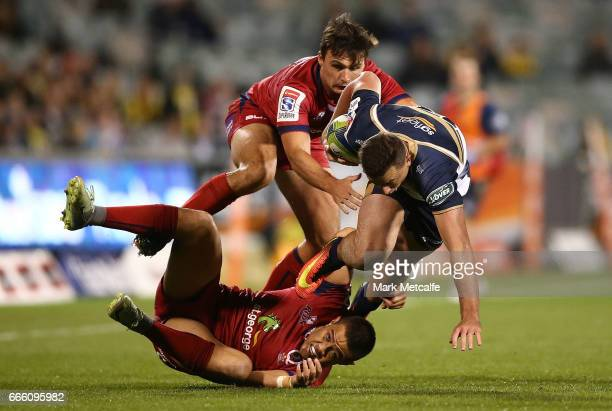 Thomas Banks of the Brumbies is tackled during the round seven Super Rugby match between the Brumbies and the Reds at GIO Stadium on April 8 2017 in...