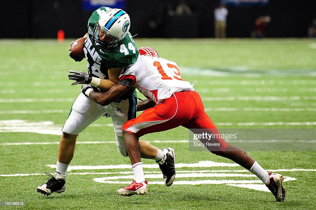 Thomas Bates #13 of the University of Houston Cougars tackles Kasey Stelly #44 of the Tulane Green Wave during a game being held at the Mercedes-Benz Superdome on November 10, 2011 in New Orleans, Louisiana.