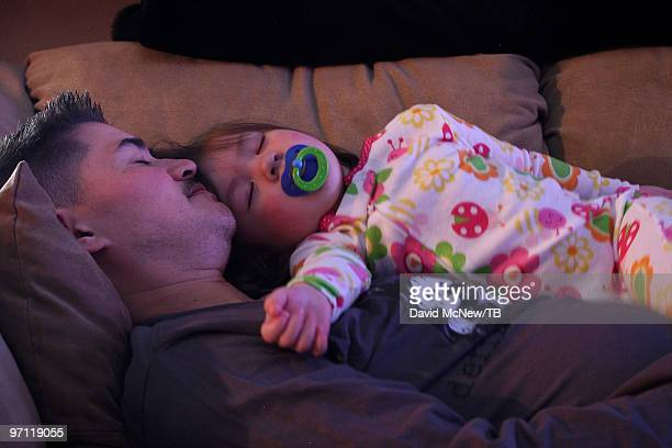 Thomas Beatie and his daughter Susan Juliette Beatie are illuminated by the glow of a television set as they fall asleep on a couch on February 17...