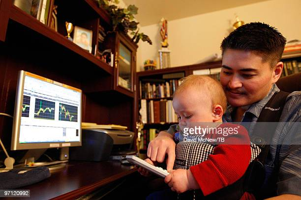 Thomas Beatie holds his son Austin Alexander Beatie who plays with a calculator as he sits down to check the stock while working from home on...