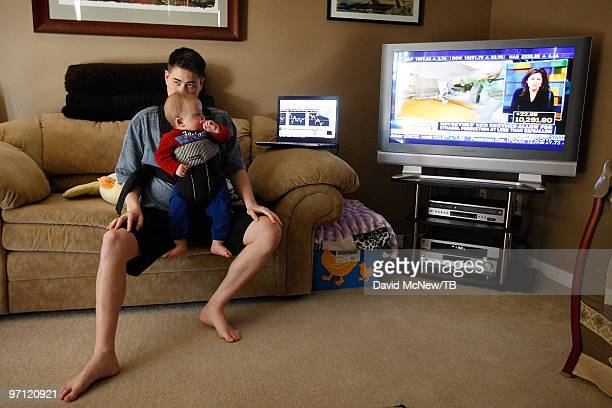 Thomas Beatie keeps an eye on the stock market while holding his son Austin Alexander Beatie as he works from home on February 17 2010 in Bend Oregon...