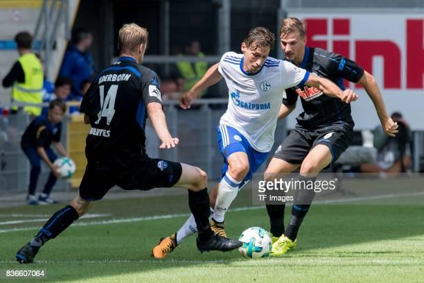 Thomas Bertels of Paderborn Benjamin Stambouli of Schalke and Sebastian Wimmer of Paderborn battle for the ball during the preseason friendly match...